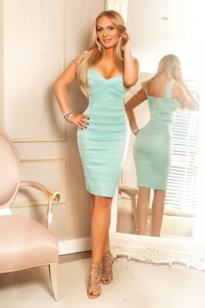 Electra stood posing in turquoise dress with hand on hip