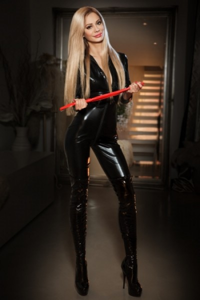Domination escort Tine wearing a latex dress with a red whip