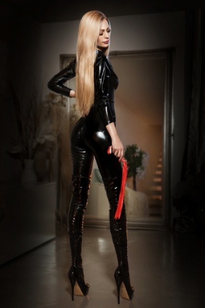 BDSM escort Tine showing off her bum in a latex outfit