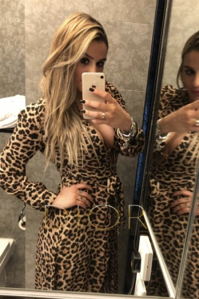 Darcie taking mirror selfie posing in lowcut leopard print dress