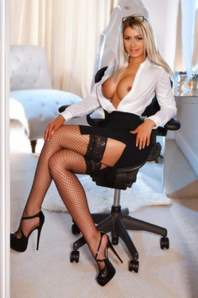 Kenya sat in sexy secretary outfit with breasts showing