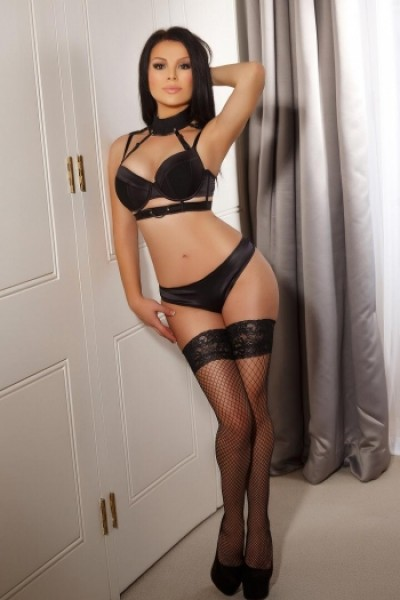 Alice posing with hand behind head in black silk lingerie set and heels