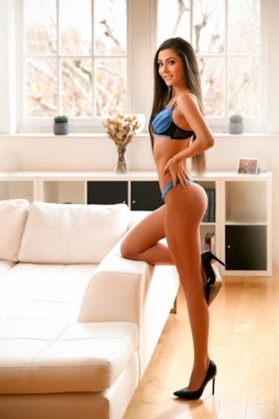 Joanna standing with leg on sofa in blue and black lingerie set with heels
