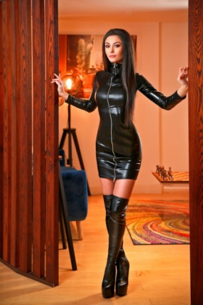 Joanna posing in doorway in tight black leather dress and heels