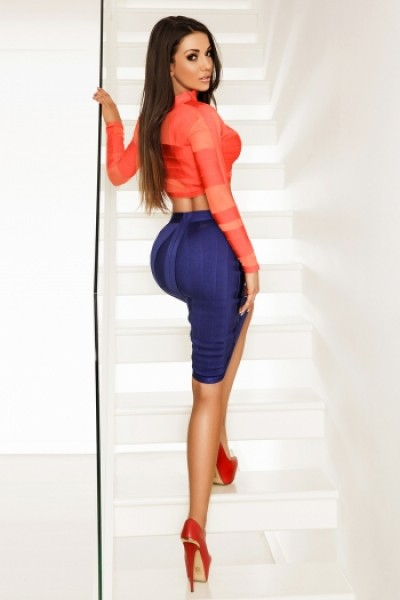 Claudete looking over shoulder in tight red and blue outfit