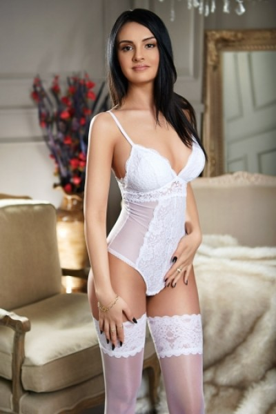 Brunette escort Marina wearing a white body with white hold ups
