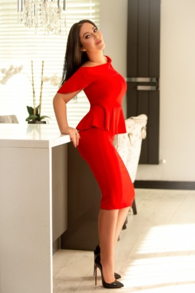 Asha wearing a sexy red dress standing in the kitchen