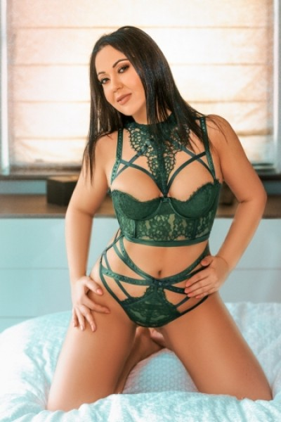 Asha kneeling down and wearing some sexy green lingerie