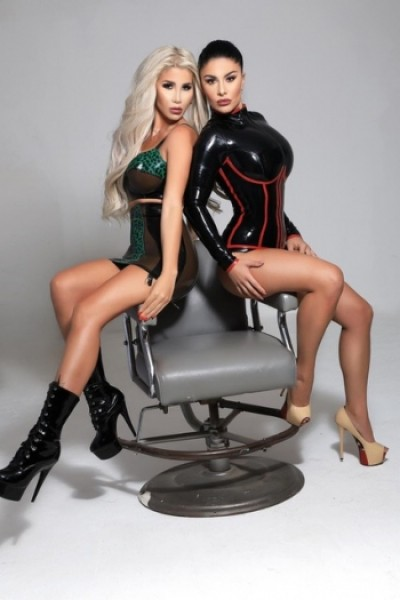 A busty blonde escort and a busty brunette one sitting on a chair