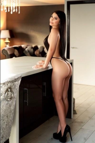 Full length picture of a sexy brunette London escort in a kitchen