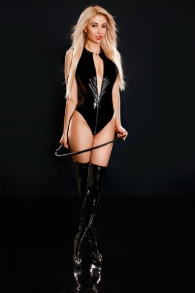 Blonde London escort Willow wearing black latex and holding a whip